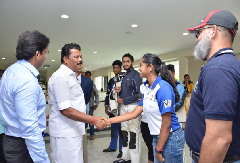 Hon'ble Minister greeting shooter Elavenil